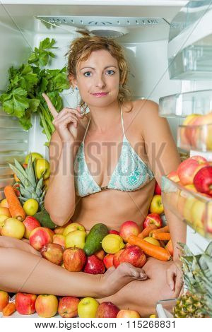 Woman sitting in a fridge in the lotus position surrounded by fruits making faces