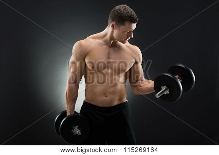 Determined Muscular Man Exercising With Dumbbells