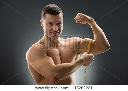 Happy Muscular Man Measuring Bicep With Measure Tape