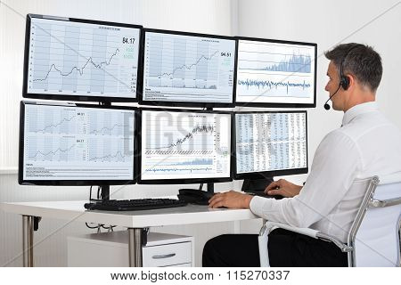 Stock Market Broker Looking At Graphs On Multiple Screens
