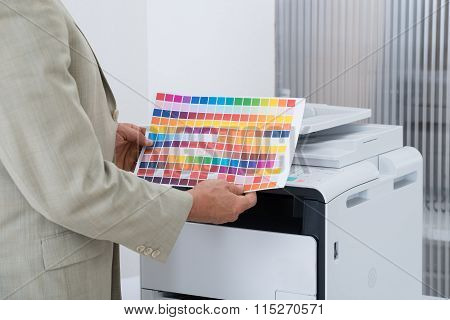 Businessman Holding Multi Colored Paper By Printer