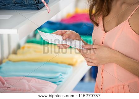 Woman Holding Receipt In Clothing Store