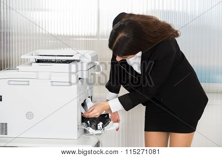 Businesswoman Removing Paper Stuck In Printer At Office