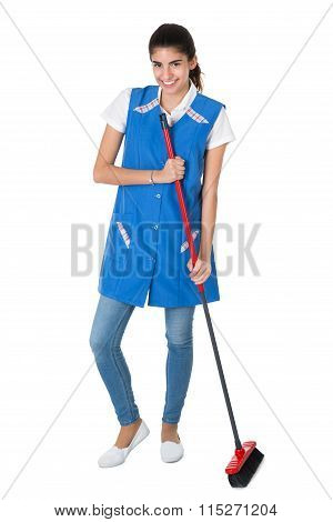 Happy Female Janitor Sweeping On White Background
