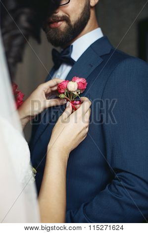 Brunette Bride Putting On Flower Boutonniere On Happy Groom In Blue Suit Closeup