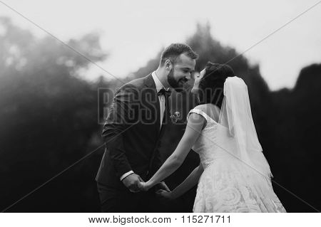 Happy, Sensual Newlywed Couple Smiling And Holding Hands In The Park B&w
