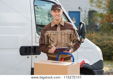 Delivery Man With Parcels And Clipboard Against Truck