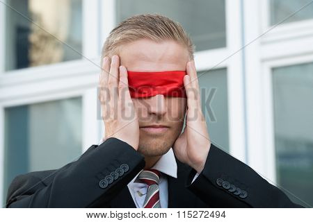 Businessman Touching Red Blindfold