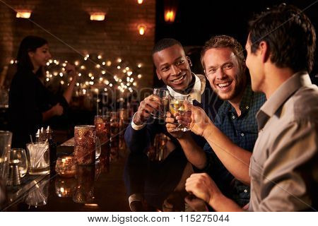 Male Friends Enjoying Night Out At Cocktail Bar
