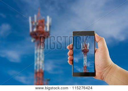 Hand with mobile phone on antenna repeater tower and sky background