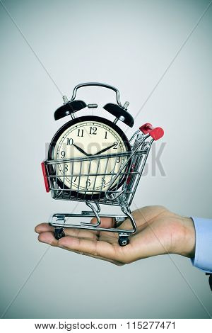 closeup of the hand of a young caucasian man holding a shopping cart with an alarm clock inside