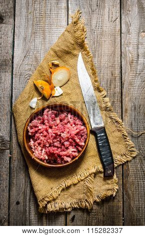 Raw Ground Beef With A Butcher Knife And A Onion.