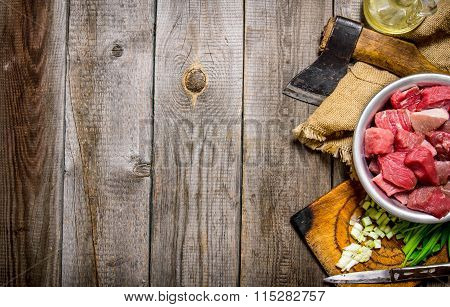 Chopped Raw Meat With Fresh Onions And An Axe On An Old Fabric.