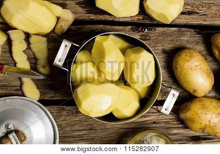 Peeled Potatoes In The Pan On Wooden Background .