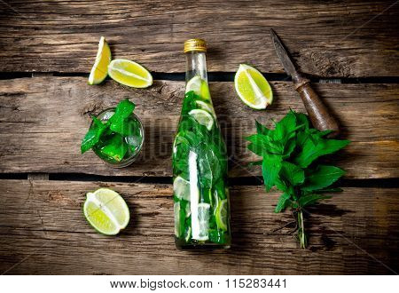 The Ingredients For The Cocktail - Limes, Mint, Knife, Is Also Prepared Cocktail In The Bottle And I
