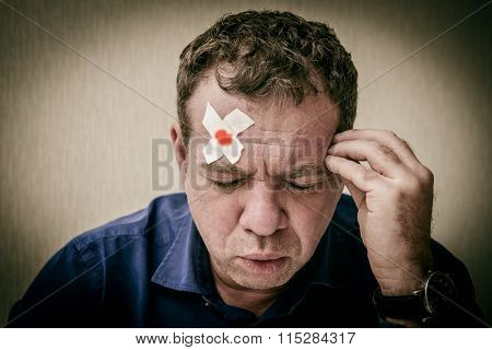 Man with adhesive plaster on his face