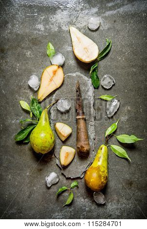 Sliced Pears With Leaves, Ice And Knife On A Stone Stand.