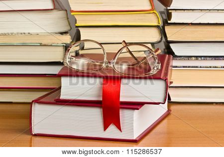 A Stack Of Books With A Red Ribbon