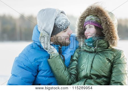 Young Woman Gently Embracing Her Husband With On Hand In Winter Frosty Day