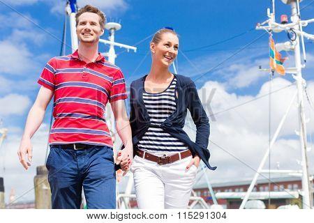 Couple enjoying vacation at German north sea ship pier running down the harbor