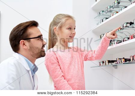 optician and girl choosing glasses at optics store