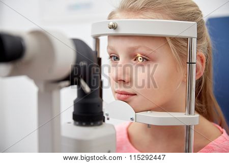 girl checking vision with tonometer at eye clinic