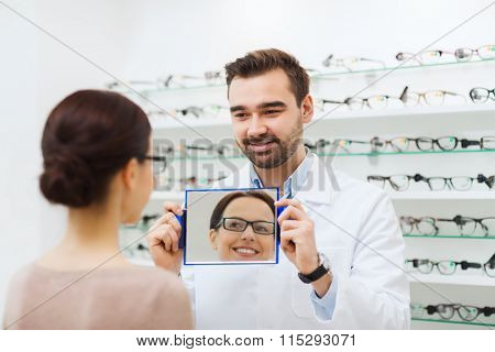 woman in glasses looking to mirror at optics store