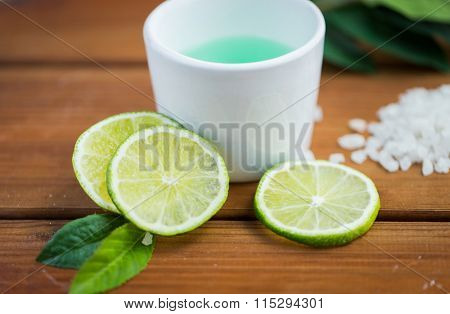 close up of body lotion in cup and limes on wood