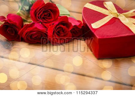 close up of heart shaped gift box and red roses
