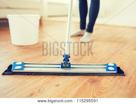 close up of woman with mop cleaning floor at home