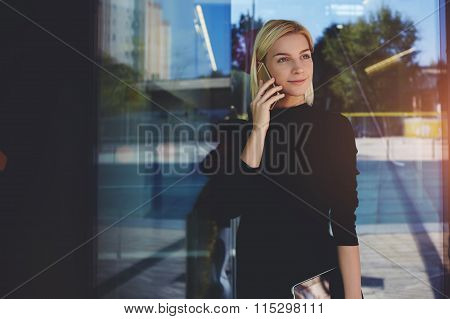 Female secretary with digital tablet in hand talking on mobile phone