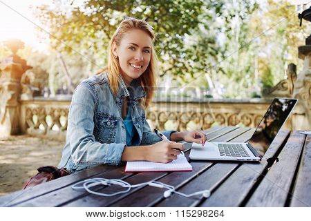 Young woman smiling to the camera while sitting with notepad and laptop computer in beautiful park