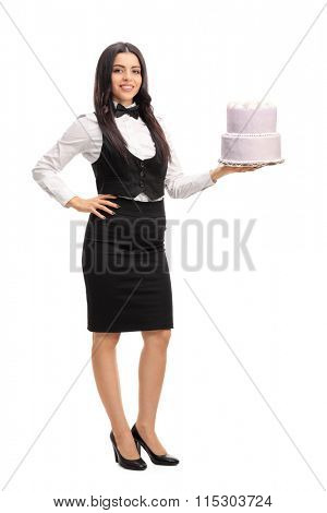Full length portrait of a young waitress holding a cake and looking at the camera isolated on white background