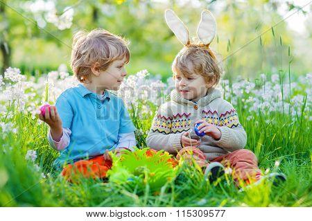 Two little kid boys on Easter during egg hunt