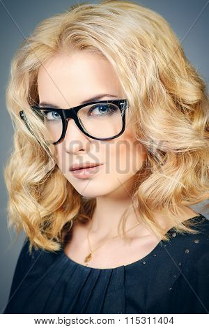 Close-up portrait of a young woman with beautiful blonde hair wearing glasses. Optics. Eyewear style.