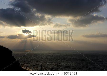 Sunset On Seashore With Dark Grey Cloudy