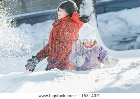 Sibling Children Making Snowstorm By Tossing Up Snow During Frosty Winter Sunny Day Outdoors
