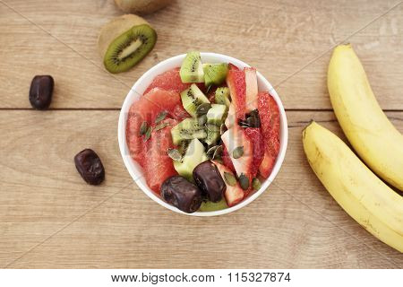 White bowl filled with fresh fruits, dried fruits, nuts, pumpkin seeds.