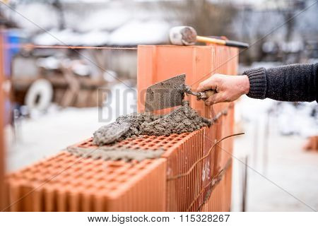 Construction Site With Worker Building Brick Walls With Mortar And Bricks