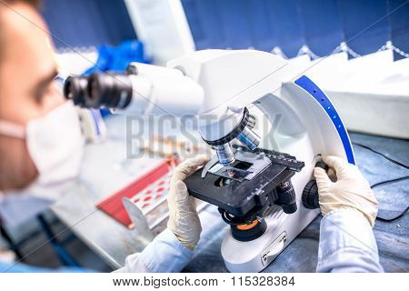 Chemist Researcher Working With Microscope For Forensic Evidence