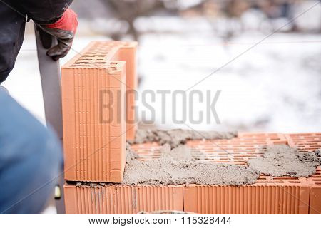 Construction Mason Worker Bricklayer Installing Brick Walls With Trowel Putty Knife Outdoors