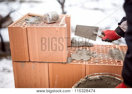 Construction Site Of New House During Winter, Man Working With Bricks And Cement, Building Walls
