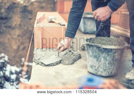 Detail Of Mason Working With Construction Spatula And Leveling Mortar For Creating Walls