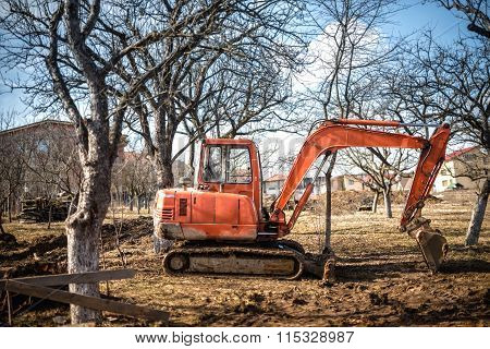 Track-type Excavator Loaderand Backhoe Working On Earth And Loading At House Construction Site