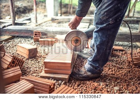 Industrial Worker Using An Grinder For Cutting And Sawing Construction Bricks