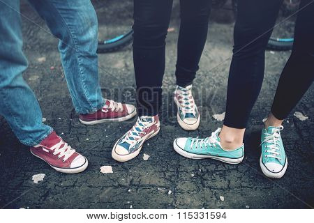 Young Rebel Teenagers Wearing Casual Sneakers, Walking On Dirty Concrete. Canvas Shoes And Sneakers