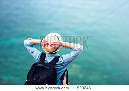 Young Woman On Summer Vacation, Hiking On Coastline And Staring At Sea Wearing Hat And Backpack