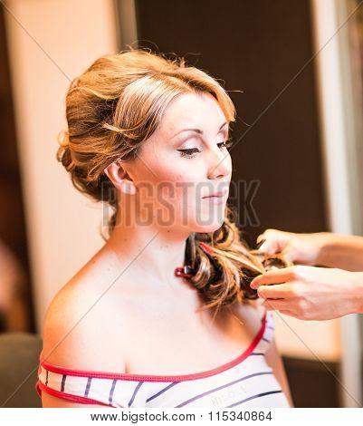 Hairdresser woman curls her hair.