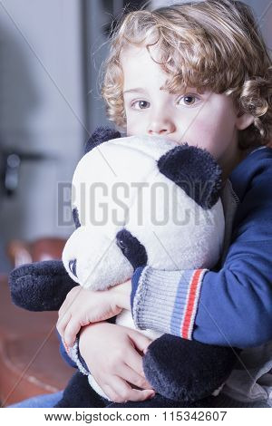 Close-up Of Lovely Blond Boy With Curly Hair Hugging Panda Toy