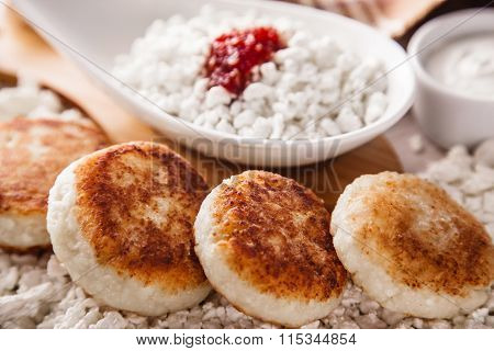 Cheesecakes, cottage cheese and jam, sour cream on a background of scattered muesli.
